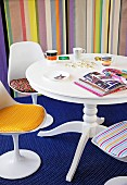 Mixture of patterns - white, round table, shell chairs with colourful seat cushions on blue patterned rug and striped wallpaper