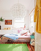 Green rug on wooden floor, bed with retro metal frame and scatter cushions, spherical lamp with many flower-shaped elements and white sideboard in background