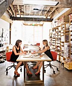 Two women sitting on red swivel chairs at conference table in industrial-style workspace