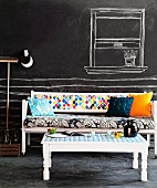 White-painted wooden bench and table with colourful mixture of textiles; wall and floor painted with blackboard paint