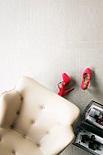 White, leather armchair, red ladies' shoes & magazine rack on white tiled floor with mixture of surface structures