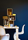 White, classic shell chairs at wooden table with crockery in shelving modules against blue wall