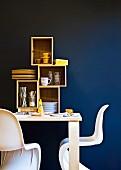 weiße Klassiker-Schalenstühle an Holztisch, darauf Regalmodule mit Stauraum für Geschirr vor blauer Wand