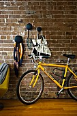 Bicycle leaning on brick wall below decorative black wall hooks for storing bags & utensils