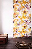 Floral length of wallpaper on white wall, vintage trunk and wicker stool