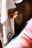 Pale brown paper flowers and rolled book pages next to patterned cushion