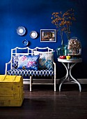 White wicker bench with floral seat cushion and scatter cushions next to glass vase of flowers on round side table against blue-painted wall; yellow wooden trunk in foreground
