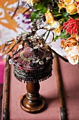 Ethnic table lamp decorated with floral ornaments next to bouquet
