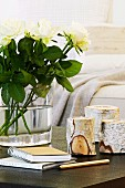 Tealight holders made from birch logs and white roses on table