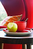 Apple with bite missing next to bowl on red plate on side table