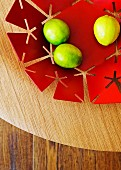 Lemons in red metal dish with perforated pattern on wooden surface