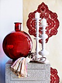 Decorative arrangement of red glass vase and white artistic candlesticks in front of ornamental wallpaper