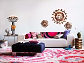 White sofa with patterned cushions, blue ottoman and Oriental rug decorated with various home accessories