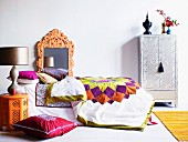 Bed decorated with quilt and multiple scatter cushions, mirror with ornate frame and ethnic-style silver wardrobe