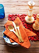 Colourful arrangement of red runner, gilt candlesticks and orange linen napkins on rustic wooden table