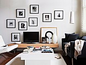 TV on designer sideboard surrounded by various black and white photos in black frames on white wall