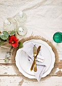 White plate, gold cutlery and linen napkin arranged with white candles and red flower on shabby-chic wooden table