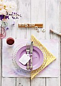 Romantic place setting with purple plate, yellow napkin, scrabble tiles and vase of spring flowers