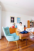 Classic pale blue armchair and woman sitting on sofa in living room with wooden floor