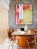 Dining area with 50s-style wooden chairs and matching table in front of modern artwork on wall and next to window with vertical wooden louvers