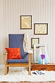 Orange patterned cushion on blue armchair with wooden frame, vases and empty picture frame on suitcase on floor below framed pictures on white wooden wall