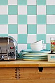 Stack of blue and yellow plates next to stainless steel toaster on wooden cabinet against turquoise and white chequered wall tiles