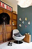 Vintage-style seating area with standard lamp, shell easy chair & books inverted on hand-made wall brackets
