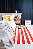 Bedroom with red and white striped carpet runner in front of black wooden paneling