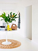White tulip table with flowers, handbag and books on a round natural fiber carpet