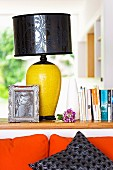 Table lamp with black shade and yellow base on partition wall