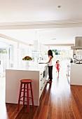 Offene Küche mit weißem Küchenblock und Retro Barhocker, Mädchen und Frau im Hintergrund