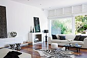 Elegant living room with light sofa, zebra skin and patio door