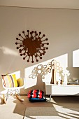 Artistic wall decoration and tree sculptures on a white lowboard next to floor cushions and a rocking chair