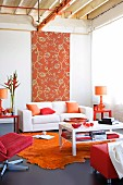 Living room - white coffee table on orange rug and grey lino floor, white sofa in front of tall floral fabric panel on wall