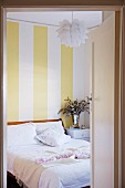 View through open door into bedroom with white bed linen, Bauhaus pendant lamp and yellow and white striped wallpaper