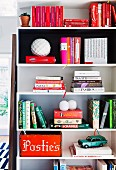 Books, vintage metal car and red-painted wooden box on and in white shelving modules on wall
