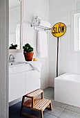 White wall tiles, wooden step stool, grey tiled floor, vintage traffic sign and towels on shelf in modern bathroom