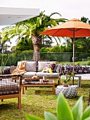 Terrace space in front of palm tree and glass balustrade, orange parasol, sofa and wicker furniture with retro flair
