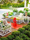 White garden sofas with orange side table on wooden terrace with retro flair by the pool