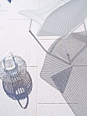 Shadow cast by white lattice chair and basket lantern on light floor tiles