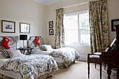 Santa Claus boots on single beds with Toile De Jouy bed linen and curtains in the guest bedroom