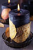 Kerze verziert mit bemalten Herbstblättern