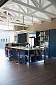 Küchentheke mit Barhockern auf Holzboden in hohem offenem Wohnraum mit weiss lackiertem Dachstuhl