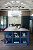 Large island counter with integrated, blue-painted shelves below ceiling lamp suspended from exposed roof structure