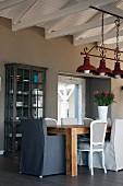 Verschiedene Sitzmöbel an rustikalem Tisch unter Vintage Hängeleuchte aus rotlackiertem Metall unter Dachstuhl