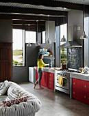 Offene Küche eines Architektenhauses mit roten Küchenfronten, Estrichboden und sichtbaren Deckenbalken
