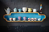 Nostalgic crockery on curved, pale blue, designer shelf on grey-painted grey wall