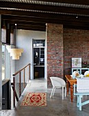 Dining area with various chairs and exposed brick wall on gallery with head of staircase