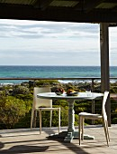 Zwei Designerstühle an rundem Vintagetisch auf überdachter Terrasse mit Blick auf das Meer