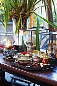 Palmenartige Pflanze zwischen antikem Teeservice auf Tablett und Totenschädel in Glasvitrine auf Holztisch in Kolonialstil